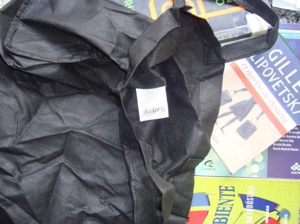 """Minha """"ecobag"""" das Lojas Americanas. Vive amassada no fundo do guarda-roupa.  Uso como mau exemplo para os alunos na aula de Moda e Sustentabilidade (Design de Moda, UFMG). Fotografei propositalmente ao lado dessa edição do Lipovetsky, com as sacolinhas pretas de compras, rs."""