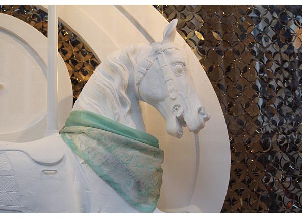 Cavalo branco sem expressão, engessado, adornado com lenço verde Louis Vuitton.