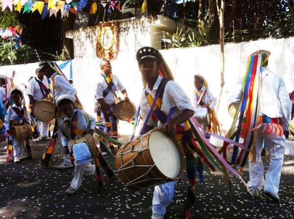 Fitas multicoloridas e longas adornam os quepes. O traje é branco pontuado de cor.