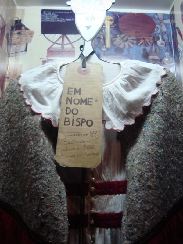 Em nome do Bispo do Rosário. Aí o uso do famoso cobertor de mendigo como um pelerine aberto / capa.